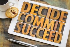 Decide, commit, succeed word abstract on tablet. Decide, commit, succeed word abstract in vintage letterpress wood type on a digital tablet with a cup of coffee stock photo