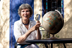 Decided where to travel next. Portrait senior lady with globe and magnifying glass, deciding on where to travel next. Enjoying her retirement Royalty Free Stock Photos