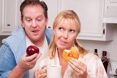 Decisão saudável comer da fruta ou da filhós Imagens de Stock
