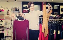 Decisión femenina de risa sobre la blusa bonita Fotografía de archivo