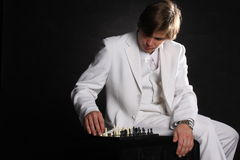 Decision. Metaphor of momentous decision: man in white suit make chess move Royalty Free Stock Photo