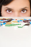 Decision. A young woman is hiding behind a table with drugs Royalty Free Stock Images