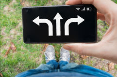 Decision concept. Man holds smartphone and is choosing direction Royalty Free Stock Photo