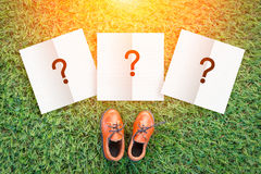 Decision concept with toy leather shoe on grass field texture ba Stock Photos