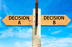 Decision A and Decision B messages, Right choice conceptual image. Wooden signpost with two opposite arrows over clear blue sky, Decision A and Decision B Royalty Free Stock Image