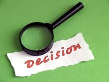 Decision, magnifier on green Royalty Free Stock Images