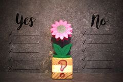 Decision making concept background with flower. Wood block with flower and words - yes, no - on grey brown background. Decision making concept. Take a choice Royalty Free Stock Images