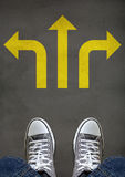 Decision Making Concept. Feet standing on a street mark of yellow arrow pointing in three different directions, concept of decision making Royalty Free Stock Photos