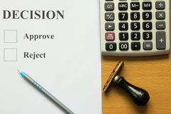 Decision paper with blue pen, calculator and rubber stamp Stock Photos