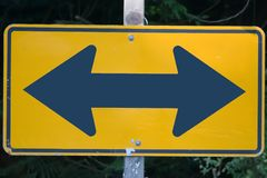 Decision road sign. A road sign showing two opposite directions to turn. Decision time royalty free stock images