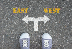 Decision to make at the crossroad - east or west. One standing at the crossroad choosing what to do next - east or west Stock Image