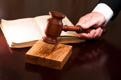 The decision was made. A hand holding a gavel and a book lying on the table Stock Photo