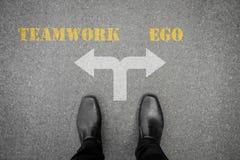 Decisione da fare - lavoro di squadra o ego Fotografia Stock