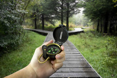 Decisions. Man holding compass with two paths ahead Royalty Free Stock Photo