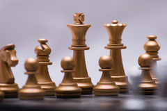 Decisive chess game. Gold chess pieces in a fierce battle stock photos