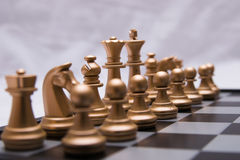 Decisive chess game. Gold chess pieces in a fierce battle royalty free stock photos