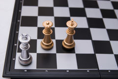 Decisive chess game. Gold chess pieces in a fierce battle stock photo
