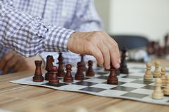Decisive chess move. Tanned wrinkled hand of old professional grandmaster making decisive chess move during intense game royalty free stock images