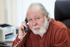 Decisive senior manager holding telephone handset and calling in office room, white beard and hair, looking at camera. Decisive senior manager holding telephone stock images