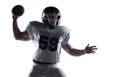 Decisive shot. American football player throwing ball standing against white background stock photography