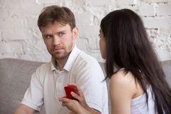 Decisive woman asking puzzled lover to marry her. Decisive girlfriend making marriage proposal to frustrated boyfriend, presenting engagement ring, feminist royalty free stock photography