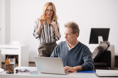 Decisive young woman seducing aged boss in the office Royalty Free Stock Image