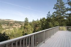 Deck. Long deck and railing with view of the trees and hills Royalty Free Stock Image