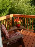 Deck and adirondack chair overlooking wooded area. Wooden deck with wooden adirondack chair, bench and geranium plant that overlooks a forested area on a sunny Stock Images