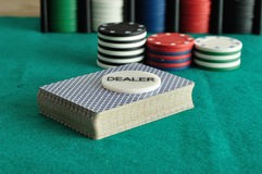 A deck of card with  poker chips. A deck of card with the dealer chip and some poker chips Stock Images