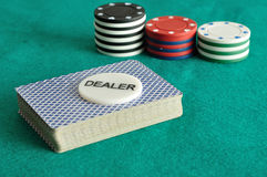 A deck of card with poker chips. A deck of card with the dealer chip and some poker chips Stock Photo