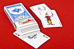 Deck of Cards. Deck of 52 cards with their package and the two jokers on royal red background Stock Photo