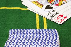 Deck of cards lying back side on a bright green canvas. Against the background of a strong combination of four kings stock photos