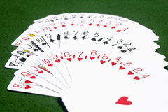Deck of cards on the table. Complete deck of playing cards laid on the green playing table according to the suits stock photos