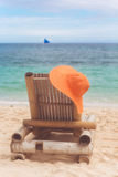 Deck chair on the beach with hat Stock Image