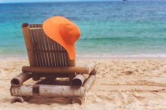 Deck chair on the beach with hat Stock Images