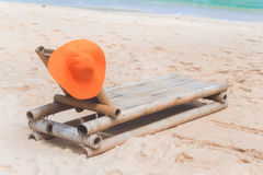 Deck chair on the beach with hat Stock Photo