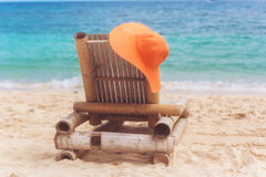 Deck chair on the beach with hat Stock Photography