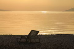 Deckchair and beautiful sunset. Deckchair on beach with beautiful sunset Royalty Free Stock Photography