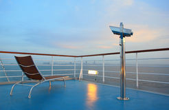 Deck-chair and binocular on ship overlooking city Royalty Free Stock Photography
