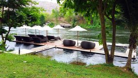Deck chair or daybeds and umbrellas on waterfront raft in resort near river Kwai Kanchanaburi, Thailand. travel and vacation in Th stock footage
