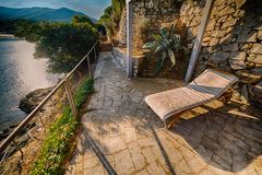 Patio overlooking the sea. Deck chair in the patio of a house overlooking the sea royalty free stock image