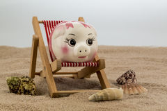 Deck chair with piggy bank Royalty Free Stock Images