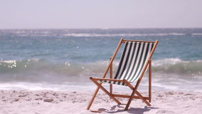 A deck chair is in the sand. On the beach stock video