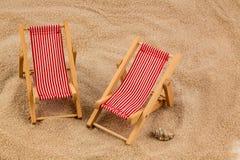 Deck chair on sandy beach Stock Photos