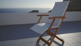 Deck Chair On Terrace In A Breeze. Empty Deck Chair On A Breezy Terrace By The Blue Sea In Summer Holiday Resort In Greece stock footage