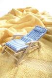 Deck chair on a towel Stock Photos