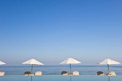Deck chair and umbrella next to infinity pool Royalty Free Stock Photo