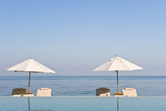 Deck chair and umbrella next to infinity pool. Deck chairs under sun umbrella between an infinity pool and the sea. Copy space provided on top stock photos