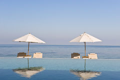 Deck chair and umbrella next to infinity pool Stock Photo