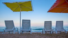 Deck chair and umbrellas on the beach stock video footage